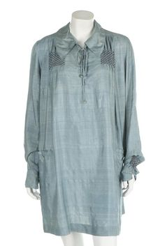 Two women's smocks. Two women's smocks. one of blue silk by Liberty & Co. Ltd, labelled, with front pockets and smocking detail, early 1920s; the other of white brushed-cotton with elaborate smocking and embroidered shoulders, c.1900; together with a copy of 'English Smocks' by Alice Armes, including patterns, 1930s (3) . Estimate:£150 - £250