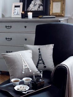 Cushions in gray linen decorated with pearl buttons stitched Eiffel Tower