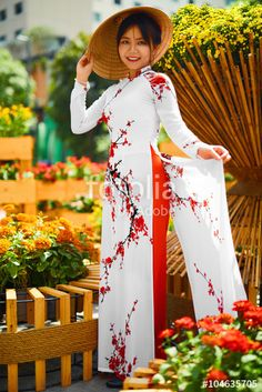 """Download the royalty-free photo """"Culture Of Asia. Beautiful Happy Smiling Young Asian Woman Wearing Traditional White Ao Dai Dress ( Clothing ), Vietnamese Conical Hat ( Non La ) Leaf Hat In Flower Garden In Ho Chi Minh City, Vietnam"""" created by puhhha at the lowest price on Fotolia.com. Browse our cheap image bank online to find the perfect stock photo for your marketing projects!"""