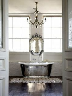 Waterworks Candide Tub - wow - like the stone walls and ebony wood floors and fab tub but the mirror and chandelier would never pass the hubby veto