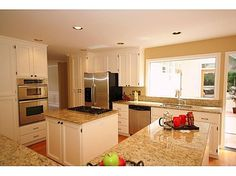 White cabinets with brown granite.