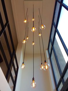 Hanglamp op maat voor in een vide met grote stalen pui. Gemaakt met 12 zwarte snoeren, mat zwarte fittingen en dimbare Tivoli led filament lampen. Edison Bulb Chandelier, Vintage Chandelier, Pendant Lamp, Pendant Lighting, Modern Chandelier, Home Lighting, Lighting Design, Indoor Stair Lighting, Living Room Lighting