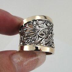 Impresionante nueva plata y oro anillo. El anillo está hecho de plata esterlina con dos pulido 9 k amarillo oro barras sobre 20 m m ancho muy rico banda de filigrana de patrón. ¡ Disfrute para siempre! Etiquetada y sellada 925. Esta belleza se le enviará en un paquete de regalo. (Todas las manchas, si son cualquiera, son debido a la cámara). Sienta por favor libre de entrarnos en contacto con en cualquier materia. Material: plata de ley 925 925 Dimensiones: Frontal Ancho: 20 mm/0,787...