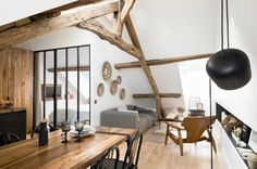 Although this apartment may be little — only 40 square meters, or 540 square feet — it has something that a lot of other little apartments don't: soaring ceilings, gorgeous exposed wooden beams, and breathtaking views over the rooftops of Paris.