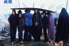 <b>1969</b> | Concert-goers huddle under a sheet of cardboard in the rain at the three-day, era-defining Woodstock Music and Art Fair in Bethel, New York. Originally published in the August 29, 1969, issue of LIFE.