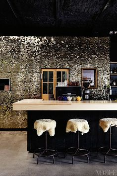 shearling stools + a shimmering wall, balanced by a neutral counter-top + cement floors - the perfect amount of glam.