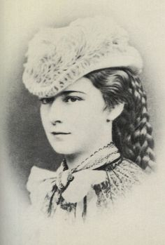 1865 Sisi smiling by Oscar Kramer  Empress Elisabeth wears a feathered hat, elaborately knotted hair, and a lace mantle held on with the possible help of a bow in this photo.