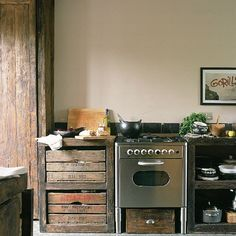 Wood, stainless steel and slate are mixed to create rustic charm with a modern edge. A tall, seamless cupboard is made from recycled scaffold planks, drawers and a wine store are made from old apple boxes. A steel cooker provides contrasting sleek lines. A black Conran Shop cooking pot, a print and wooden accessories further combine old and new elements.