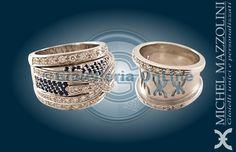 due anelli della collezione City by Night. Anello in oro bianco con diamanti e zaffiri, logo in rilievo. Anello in oro bianco con diamanti e logo traforato.