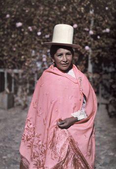 Una mujer boliviana joven posa en su sombrero de paja blanco, alto.