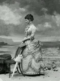 Woman photographed as if at the beach, 1882. You can tell it's just a studio background.