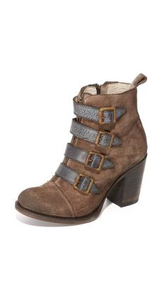 Distressed leather straps and an antiqued buckle cover the front zip on these suede FREEBIRD by Steven booites. Exposed zip at the side and a pull tab at the top line. Stacked heel with rubber patch. Leather sole.