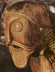 Carved Head from Oseberg Ship Burial. Is he wearing i hereforto unknown helmet style with mail aventail? Or is it an ugly hat?