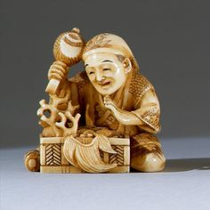 "IVORY NETSUKE Mid-19th Century By Shugyoku. In the form of a seated man exploring a box filled with implements representing the Gods of Good Fortune. Signed on inset plaque. Height 1.5"" (3.6 cm)."