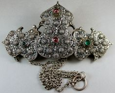 Silver filigree with domes, flowers, and brilliant glass stones. Traces of original gilding. The V&A dates this from 1750-1850. http://collections.vam.ac.uk/item/O79246/clasp-clasp-unknown/  Note the six-petal flower design underneath the lower three stones. I have seen versions of this where the six-petal flowers are reworked into six-pointed Jewish stars. I wonder if the silversmith was Jewish.  Lynn via Ethnic Jewels