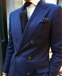A fun dark navy polka dot pocket square decorates this indigo double-breasted blazer.