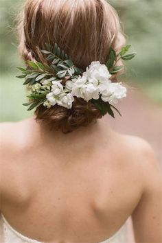 Wedding updo hairstyle with greenery and white flower