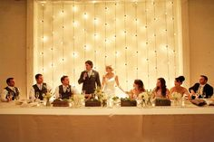 Create a soft, romantic backdrop for a long head table with string bulb lights glowing against neutral walls and tablecloth.