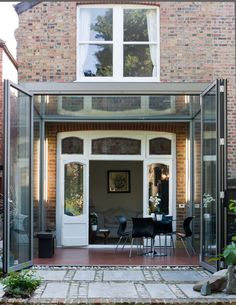 A frameless glass box extension with aluminium bifold doors.