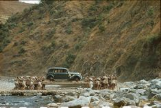 1950- Porters transport a car on long poles across a stream in Nepal. Photograph by Volkmar K. Wenztel.