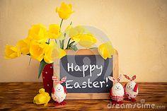 Huevos de Pascua, flores y espacio en blanco de la pizarra en la tabla de madera Concepto de los días de fiesta de la primavera.