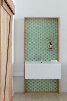green penny tile accent wall in contemporary bathroom with wall hung vanity