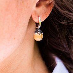"""Die Perle aus Eschenholz ist mit einer Sterlingsilber-Blüte eingefasst. Der schlichte Baguette-Schliff verleiht dem Design  Eleganz, sodass die """"Blütenmeer""""-Ohrringe für festlichen Anlässe aber auch als Accessoire für jedes Outfit einfach perfekt passen."""