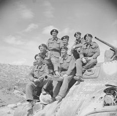 Tank men ready for the road. Note the inscriptions on the tank, Alamein and Tripoli are scored out and Tunis appears to be the next stop.