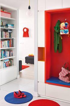 """W przedpokoju projektant stworzył oryginalny mebel – obramowane białymi szafkami czerwono-niebieskie siedzisko. To """"okienko"""" pozwala usiąść, wygodnie założyć buty i skorzystać z wieszaków. Mała wnęka służy do odkładania kluczy i poczty. W holu znalazł się też regał z książkami."""