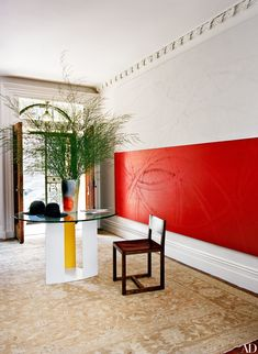 An entryway's traditional architecture is juxtaposed with a red monumental painting by Young   archdigest.com