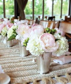 wedding centerpiece with light pink peonies and white hydrangeas in silver vases
