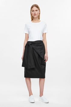 A slight cocoon shape, this skirt is made from a comfortable cotton-mix with a slight stretch. Tied at the waist, it has an asymmetrical front drape, in-seam pockets and a single back vent.