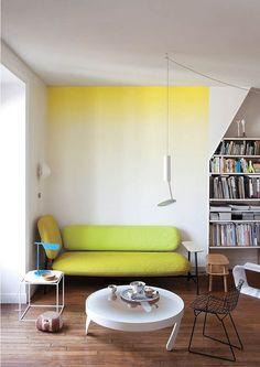 parede com efeito ombré, pintura em degradê em amarelo e branco, sofá amarelo, mesa de centro branca, piso de madeira