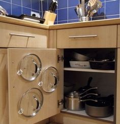 Self-sticking 3M Command hooks hold pot lids in place and keep them from getting lost in the back of the cabinet.