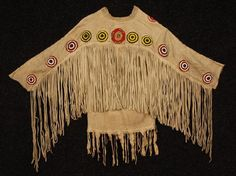 NATIVE AMERICAN LAKOTA GHOST DANCE SHIRT, 20th C. Fring  - NATIVE AMERICAN LAKOTA GHOST DANCE SHIRT, 20th C. Fringed buckskin decorated across sleeves and shoulders with a repeat of beaded bullseye roundels, three roundels on shirt front. Chest 44, shoulder 26, sleeve 23
