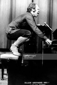 british-singer-elton-john-standing-on-his-piano-stool-during-a-in-picture-id109766222 (695×1024)