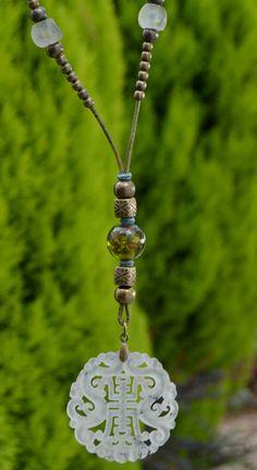 Colgante oriental de jade color marfil con cuentas de cristal verde, cuentas de cristal reciclado africano azules, cuentas metálicas y cuero redondo color frambuesa. Cierre de zamak bañado en...