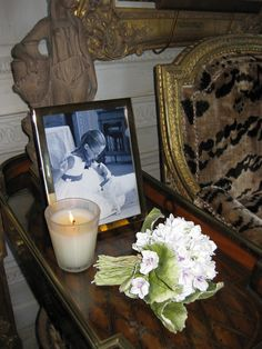 "Howard Slatkin only burns Nest Fragrances scented candles at home.  Here, in his New York living room, is Nest's ""Bamboo"" candle, on a French Louis XVI table, next to a photo of his neice Ali and a sculpture of a bouquet by artist Clare Potter."