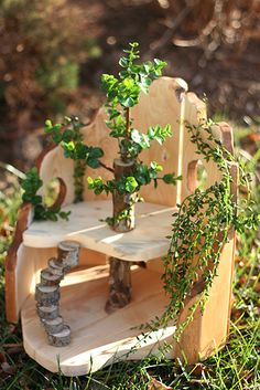 How a fairy house was created using wood and scraps from the garden along with fake greenery.
