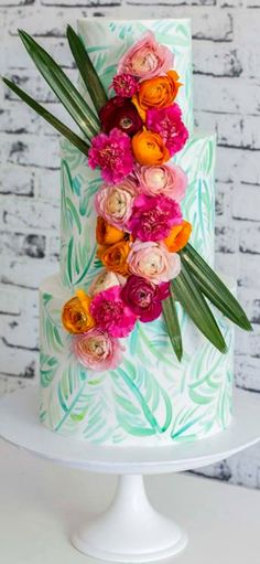 Hand painted leaves on cake with bright colored flowers.