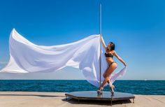 Фото: Female pole dancer against the sea and sky
