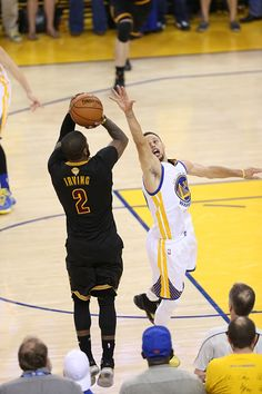 Kyrie Irving of the Cleveland Cavaliers shoots the game winning three pointer against Stephen Curry of the Golden State Warriors for the Game Seven...