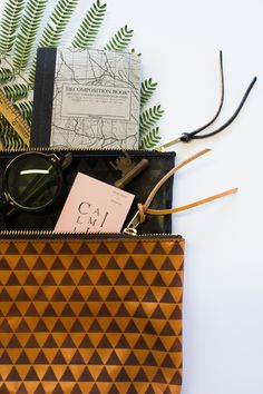 the sons & daughters laser engraved leather triangle clutch, available in black, brown, and cognac - for all the unique things that you want to tote around town with you - available now at www.camilliaheirloom.com