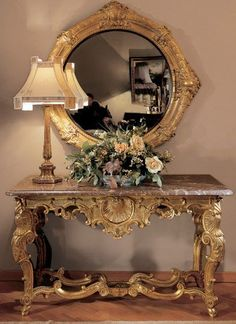 Baroque Style table with mirror. Overly gilded and ornate. The X frame stretcher is still at the bottom and not yet integrated into the table top. The shell motif was also popular.