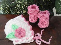 Touca e bota para deixar sua bebê bem quentinha. <br>Feito em crochê com lã antialérgica para bebê, tem uma flor com pérola no centro e folhas. <br>A touca é bicolor então coloquei fotos com bota branca e rosa, mas só vai uma, você tem que escolher. <br>O Kit é composto por uma touca e um par de botas. <br>Tamanhos (circunferência da touca): <br>1-3 meses (38-40 cm) <br>3-6 meses (42-44 cm) <br>Tamanhos: sola <br>8 cm - RN <br>9 cm - 1 a 3 meses <br>10 cm - 4 a 6 meses <br> <br>Cor- da foto…