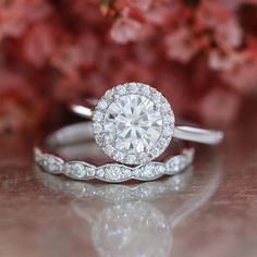 This bridal wedding ring set showcases a 7mm round cut Certified Charles & Colvard Forever One Moissanite engagement ring set in a solid 14k white
