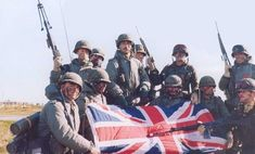 Argeninian soldiers pose with a UK flag captured.