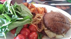Slimming World SP Dinner.  Burger using a large flat mushroom as a bun with fried onions, salad, roasted tomatoes and roasted butternut squash