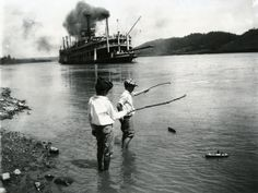 Children playing with toy boats on the river's edge as a steamboat passes in Rising Sun, Indiana, 1919. (Photo by Felix Koch/Cincinnati Museum Center/Getty Images)
