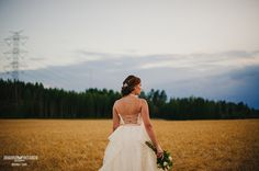 Lace wedding dress, open back, straps, bride in a field. Dress by Pukuni (www.pukuni.fi)